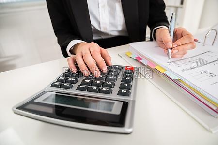 geschaeftsfrau macht finanzberechnung am schreibtisch