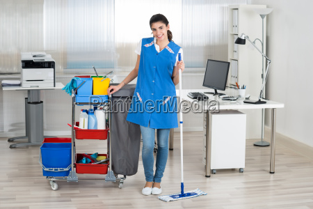 happy female janitor mopping floor in