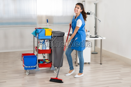 happy female janitor cleaning floor with