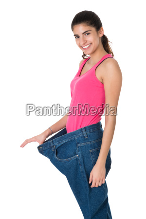 smiling woman showing her old jeans