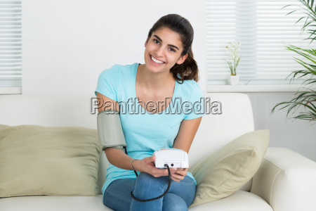 happy woman checking blood pressure on