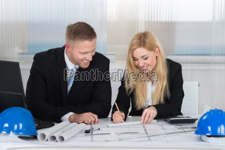 architects discussing over blueprint in office