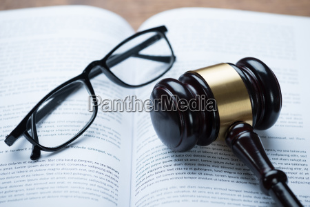 mallet and eyeglasses on open legal