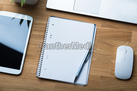 notepad and pen with technologies on