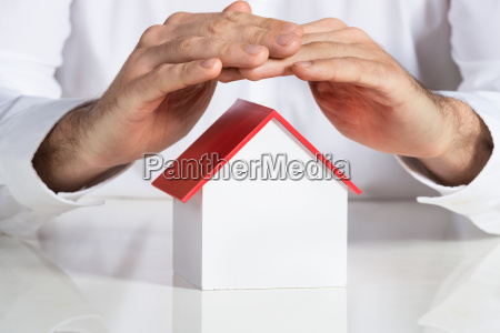 businessman protecting house model at office