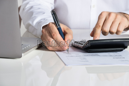 businessman calculating invoice by laptop