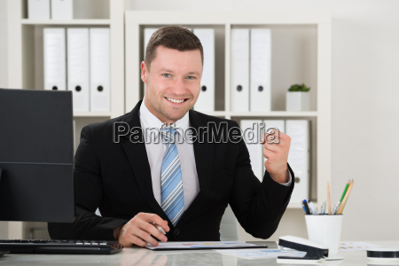 happy businessman clenching fist at desk