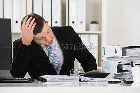 tensed accountant sitzen am schreibtisch im