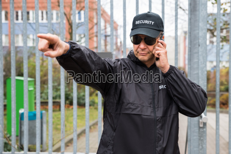 security guard gesturing while using walkie
