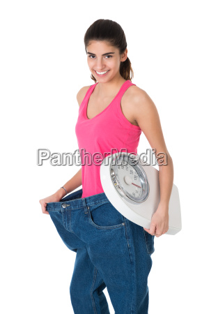 smiling woman with weight scale showing