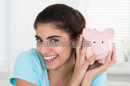 happy woman holding piggy bank at