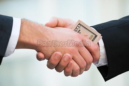 businessman bribing partner while shaking hand