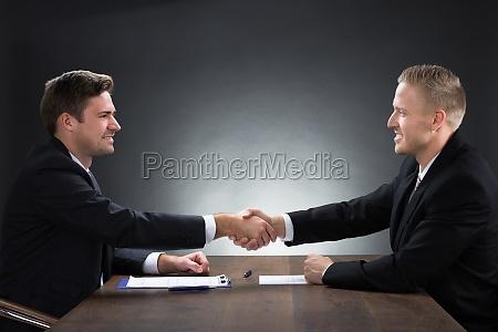 young businessmen shaking hands at desk