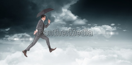 composite image of businessman jumping holding