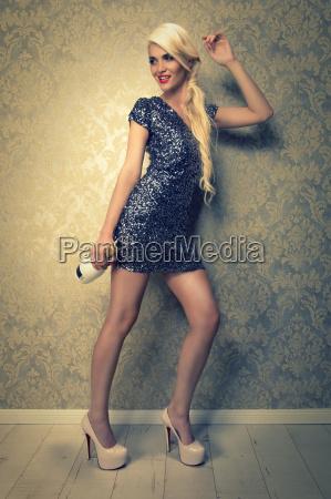 attraktive blonde frau im kurzen pailettenkleid