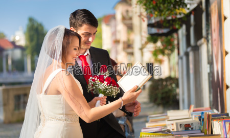 beautiful wedding couple reviewing vintage books