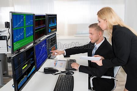 finanzagenten die computerbildschirme im buero ueberwachen