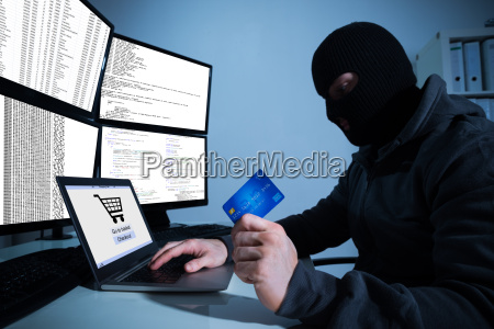 hacker holding credit card while using