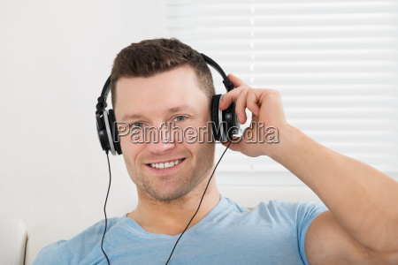 laechelnder mann hoeren von musik ueber