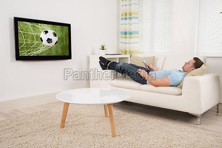 entspanntes mann aufpassendes fussballspiel zu hause