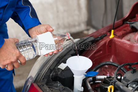 worker pouring water into windshield water