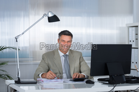 smiling accountant using calculator while writing