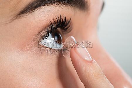 frau traegt kontaktlinsen zu hause