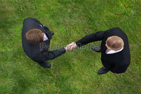businessmen shaking hands while standing on