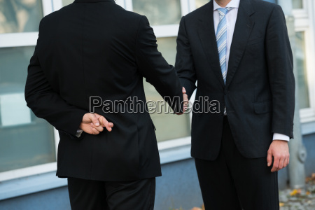 dishonest businessman shaking hands with partner
