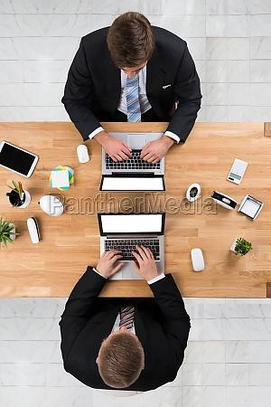 businessmen using laptops at desk in