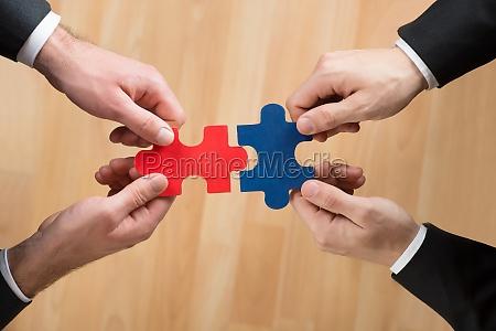cropped image of businessmen assembling jigsaw