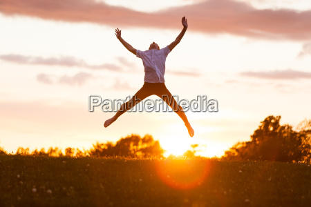boy jumping high for happiness against