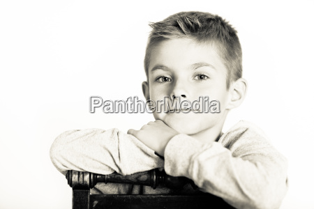 cute boy leaning on a chair