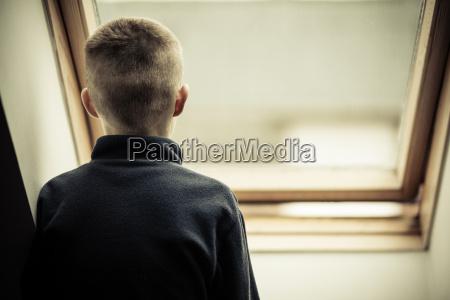 einsamer junge junge blick durchs glasfenster