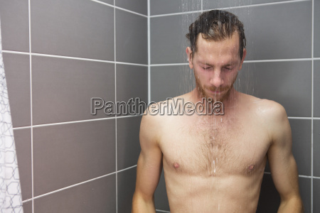 red haired man taking a shower
