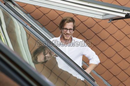 junger mann aus einem dachfenster suchen