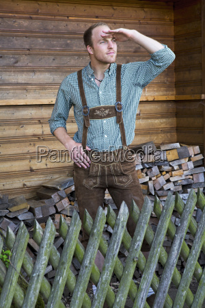 young man in lederhosen looking into
