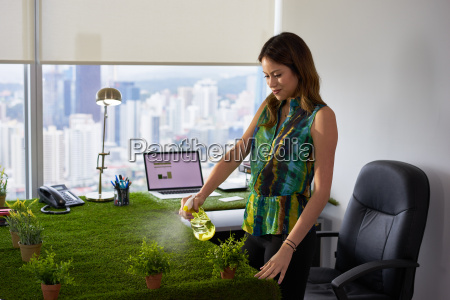 ecologist business woman watering plants in