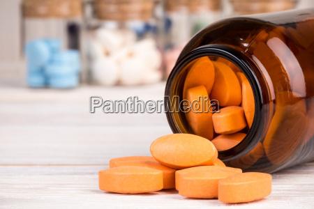 orange pillen in glasbehaelter mit medikamenten