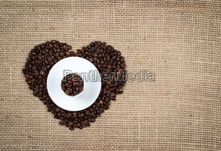white cup on heart coffee beans