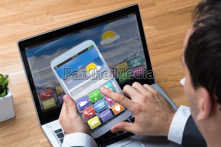 businessman using smartphone and laptop at