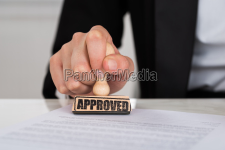 businesswoman stamping approved on contract paper