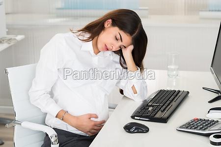 upset pregnant woman sitting at computer