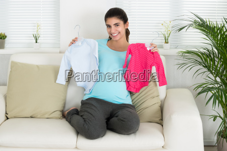 happy pregnant woman holding baby clothes
