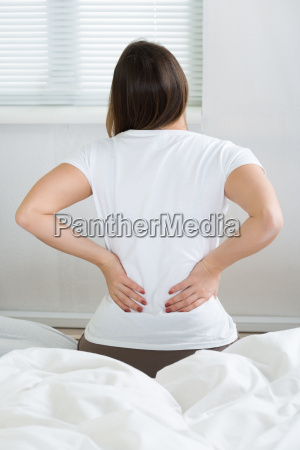 woman with back pain sitting on