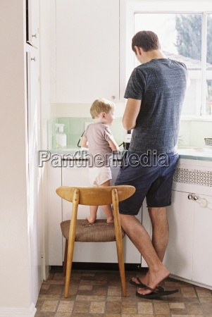 man standing in a kitchen his