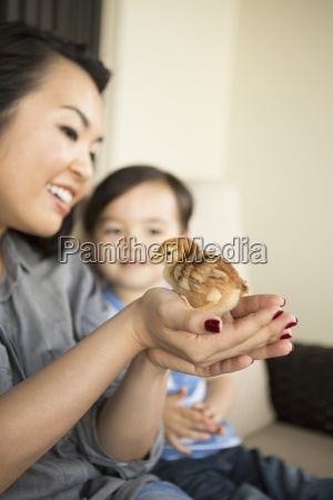 smiling woman holding a tiny chick