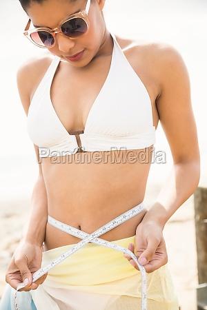 pretty woman in bikini measuring her