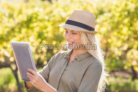 smiling blonde woman using a tablet
