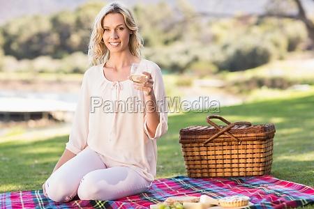 smiling blonde woman sitting on picnic